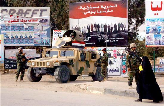 Soldados iraquíes montan guardia en una calle junto a carteles electorales en los comicios que se celebraron es sábado pasado bajo la ocupación estadounidense. EFE