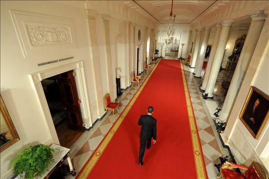 Obama caminando solitario hacia la rueda de prensa donde anuncio la aprobación del plan de estímulo de 825.000 millones de dólares. EFE