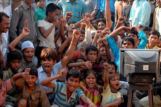 EFE.- Los niños vecinos del actor Mohammed Azharuddin Ismail siguen la ceremonia de entrega de los Óscar