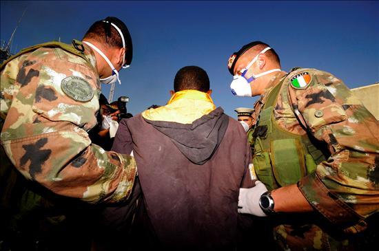 Militares italianos trasladando a un inmigrante. EFE